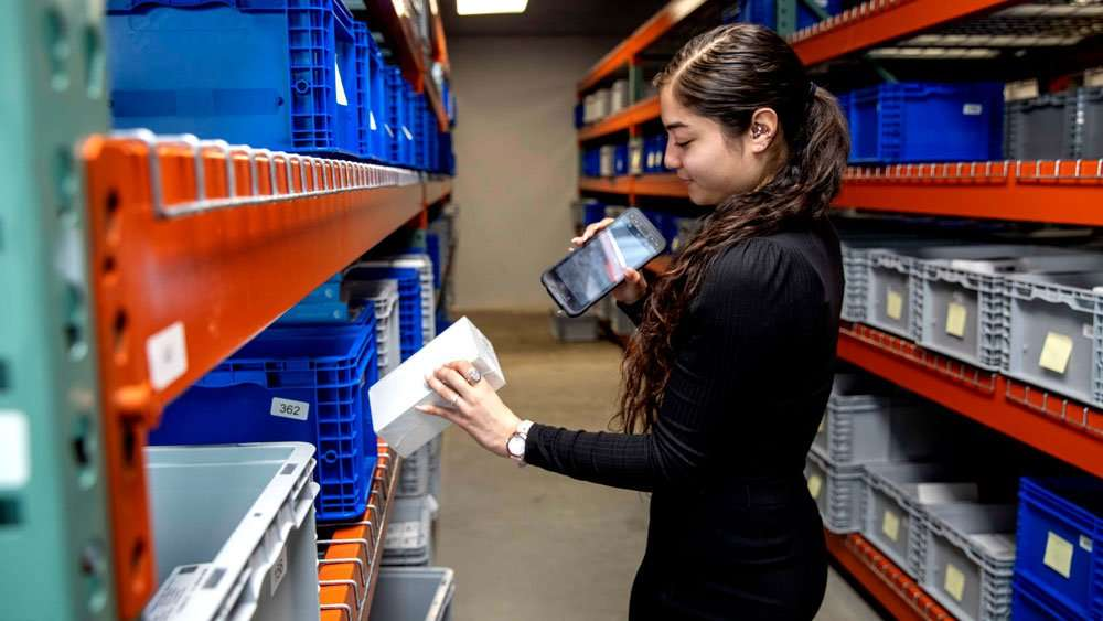 Sonim RS60 with Girl in Warehouse and product
