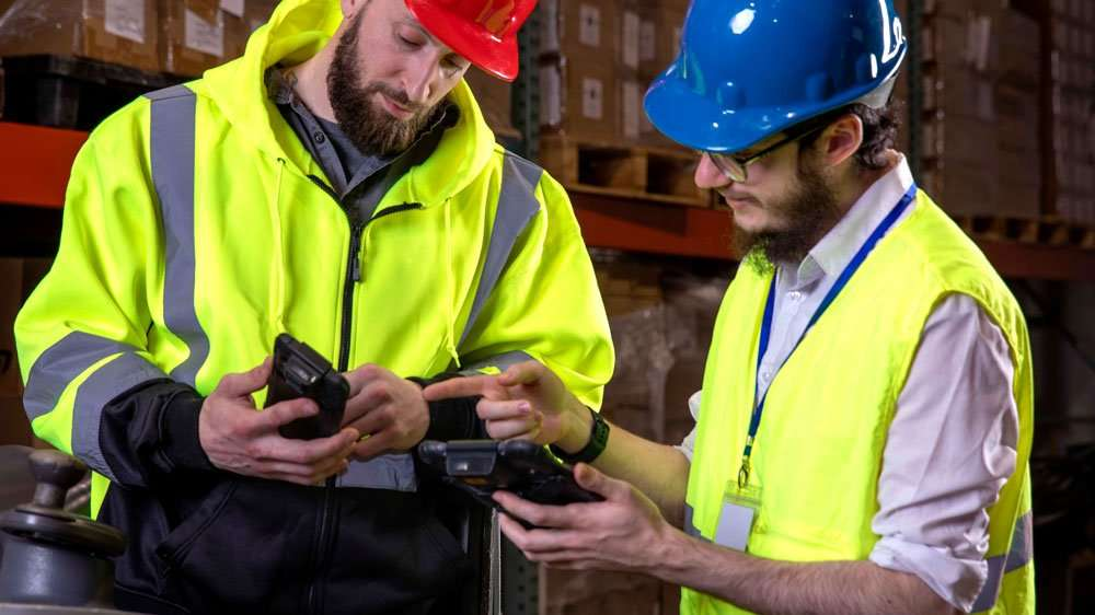 Sonim RS60 with two workers in warehouse