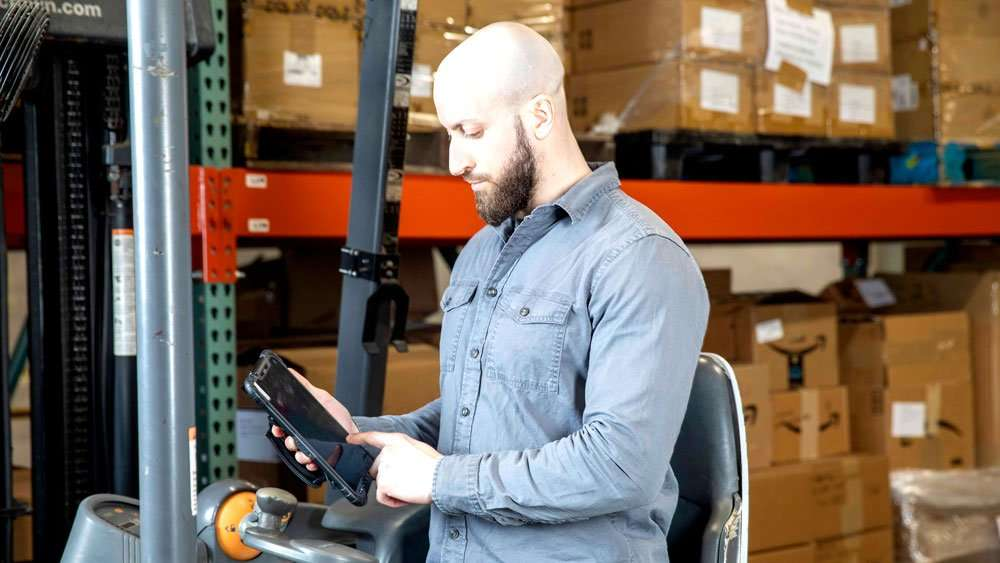 Warehouse worker using the Sonim RS80 Mobile Computer for Inventory Management